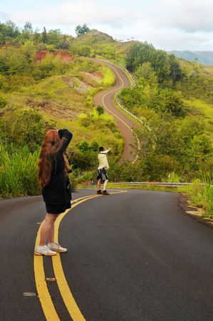 striping: Two photographers getting shots of a windy road in Hawaii Stock Photo