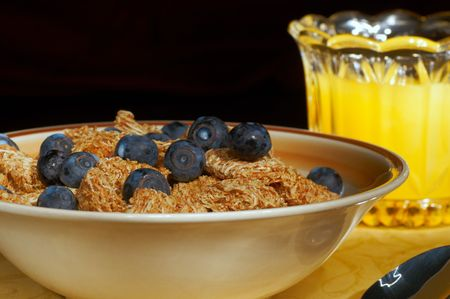A glass of orange juice behind a bowl of cereal with blueberries photo