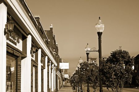 main: Storefronts, sidewalks, and lamp posts in small-town America, monochrome, sepia