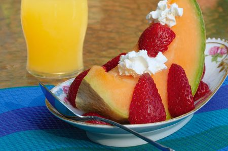 A fresh slice of melon garnished with strawberries and dollops of whipped cream on a fancy dish photo