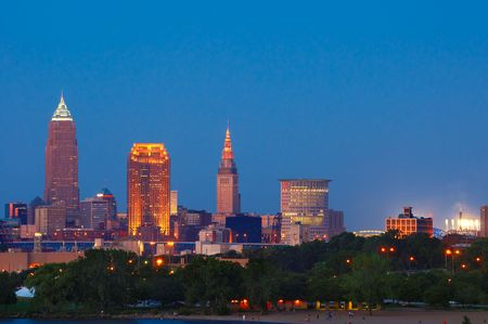 Downtown Cleveland lit up at dusk, with stadium lights at right photo