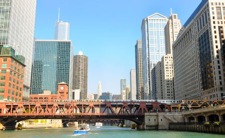 Buildings and bridges, with an elevated train, looming above the Chicago River Stock Photo