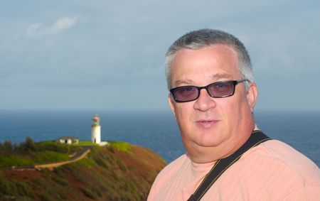 graying: A man framed by the sea and a lighthouse Stock Photo
