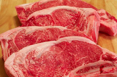 Four strip steaks laid out on a on a cutting board Stock Photo - 6485125