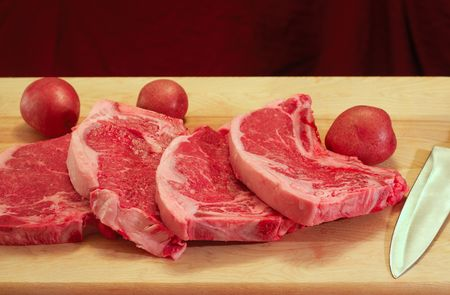 Four strip steaks on a cutting board, with red potatotes and butcher knife photo