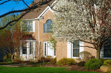 midwest usa: A beautiful home in the early spring with flowering cherry tree