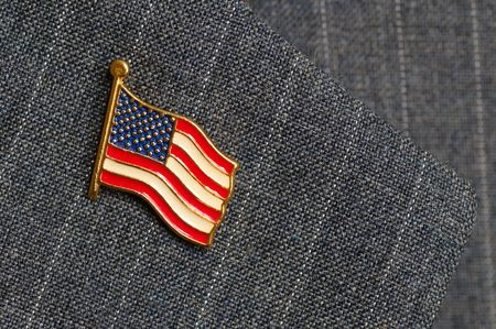 An American flag lapel pin on a pinstripe suit lapel photo