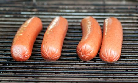 Four hot dogs just beginning to cook on a charcoal grill photo