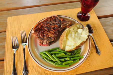 A dinner of grilled strip steak, baked potato, and green beans set on a picnic table photo