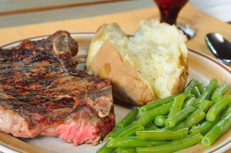 A low angle view of steak with baked potato and green beans