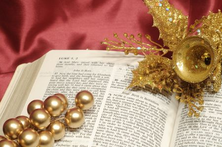 Bible open to the Christmas passage of Luke 2 with gold berries and bell photo