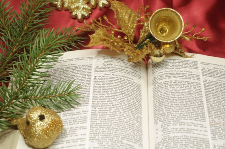 religious text: Bible open to the Christmas passage of Luke 2 with evergreen and gold decor
