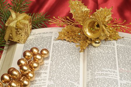 Bible open to the Christmas passage of Luke 2 with gold berries, gift box, and bell photo