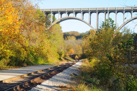 A passenger train rounds a curve and approaches under a high arch bridge in a scenic area photo