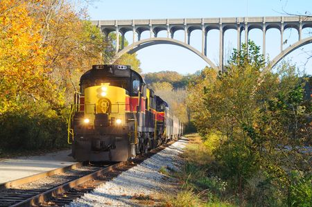 An oncoming passenger train under a high arch bridge in a scenic area Stock Photo
