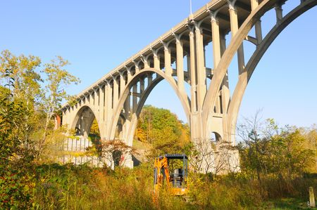 A high arched bridge in morning sunlight spanning a wide valley with a backhoe in foreground Stock Photo - 8050801