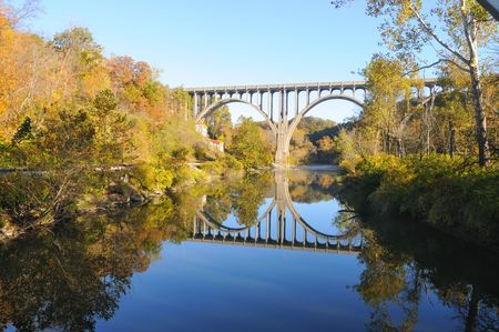 A high arched bridge reflected in a deep blue river in autumn Stock Photo - 8050803