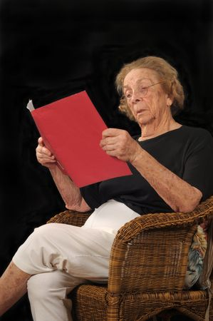 reading material: Senior adult woman skeptically reading material in a loose-leaf folder Stock Photo