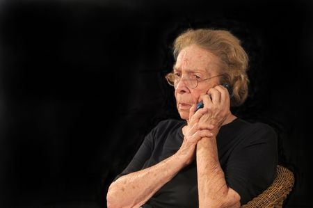 fear: Grandmotherly woman hearing bad news on a cell phone