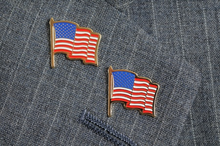 A pair of American flag pins on a pinstripe suit lapel photo