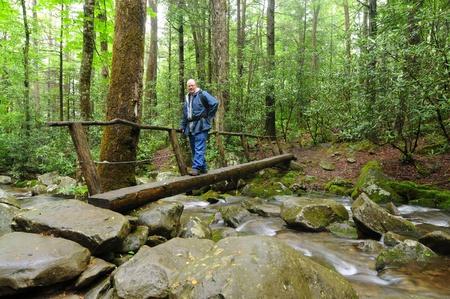 A man crosses a narrow footbridge over a rushing stream photo