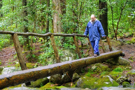 A man gingerly crossing a narrow footbridge over a rushing stream photo