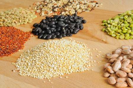 Selection of dry foods--red and white quinoa, lentils, peas, beans, and wild rice--on a cutting board photo