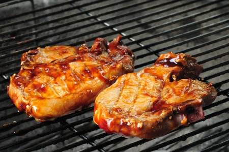 pork chop: Two bbq pork chops finishing on the grill Stock Photo