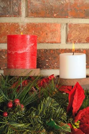 mantel: Due candele festa di Natale con verde su una mensola con sfondo di mattoni