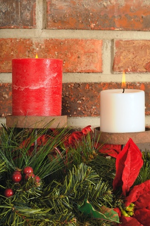 mantel: Two festive Christmas candles with greenery on a mantel with brick background