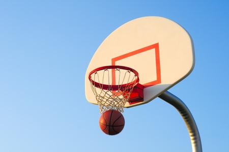 A basketball shot drops through an outdoor net photo