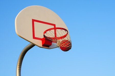 A basketball shot swishes through an outdoor hoop photo