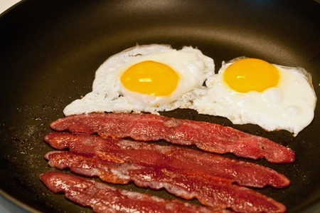 pan fried: Fried eggs and bacon cooking in a skillet