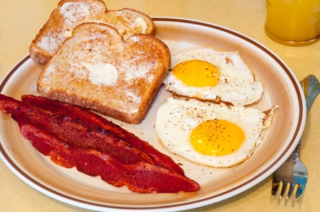 sunny side up: Simple breakfast of fried eggs, bacon, toast, and juice Stock Photo