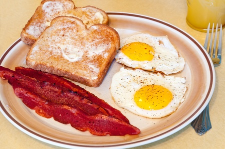 bacon and eggs: A breakfast of fried eggs, turkey bacon, toast, and juice