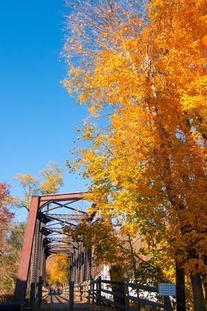 northeast ohio: Old pedestrian bridge under brilliantly colored trees in autumn Stock Photo