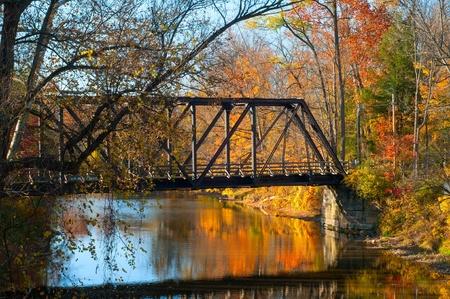 northeast: An old pedestrian bridge over an autumn-hued stream
