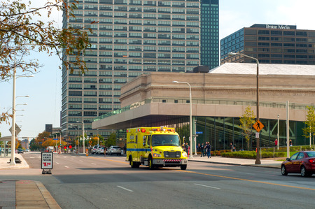 archtecture: Cleveland, OH - October 5  An EMS ambulance races down the street having just passed the recently opened convention center in Cleveland Ohio   People are gathering for an exhibit in the convention center