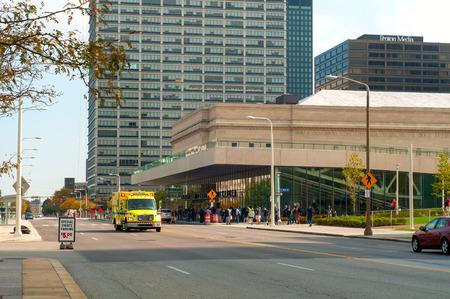 archtecture: Cleveland, OH - October 5  An EMS ambulance races down the street in front of the recently opened convention center in Cleveland Ohio   A crowd can be seen queuing up for an exhibit in the convention center