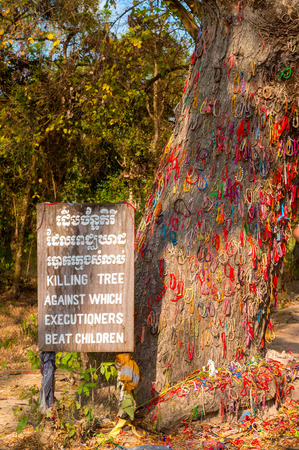 festooned: PHNOM PENH, CAMBODIA - FEBRUARY 28, 2014: A tree that was used for killing children is festooned with memorial ringlets at the Choeung Ek Genocidal Center, commonly known as the Killing Fields. The center memorializes the thousands of victims who died her