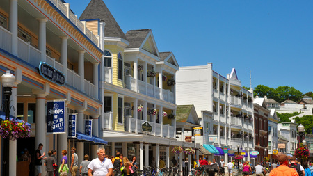 mackinac: MACKINAC ISLAND, MI - JUNE 26, 2014: Main Street on Mackinac Island is thronged with tourists on a bright summer day. Fort Mackinac is visible at upper right.