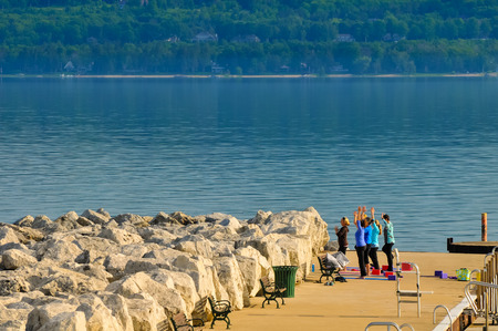 traverse: BAY VIEW, MI - JUNE 26, 2014: A pier on Little Traverse Bay off Lake Michigan becomes a good place for early-morning calisthenics. Bay View is next to the popular resort town of Petoskey.