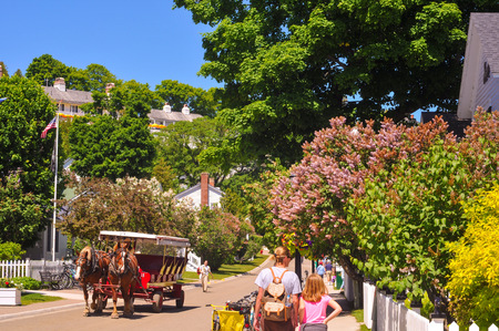 mackinac: MACKINAC ISLAND, MI - JUNE 26, 2014: A horse-drawn cab and pedestrian visitors amble along flowery Market Street on a sunny summer day.