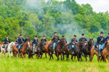 hale: BATH, OH, USA - AUGUST 9, 2014: Union cavalry troops ride by in parade after victory in the 3rd Battle of Winchester (1864) in a Civil War reenactment at Hale Farm and Village in Ohio.