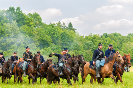 cavalry: BATH, OH, USA - AUGUST 9, 2014: Union cavalry troops ride by in parade after victory in the 3rd Battle of Winchester (1864) in a Civil War reenactment at Hale Farm and Village in Ohio.