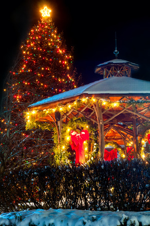 evergreen wreaths: A village Christmas tree and gazebo are festively lit up for the holidays Stock Photo