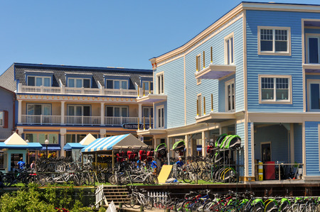 awnings: MACKINAC ISLAND, MI - JUNE 26, 2014: Picturesque buildings and rows of bicycles greet visitors stepping off the ferry at Mackinac Island, a popular summer tourist destination. Editorial