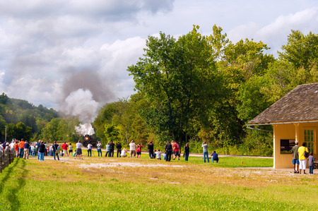 mill valley: BRECKSVILLE, OH - SEPTEMBER 6, 2014: Passengers wait for a photo op as the steam train approaches on a run-by at Boston Mill station on the Cuyahoga Valley Scenic Railroad, part of the annual Steam in the Valley.