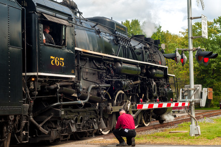 flashers: BRECKSVILLE, OH - SEPTEMBER 6, 2014: A railroad employee kneels by the track as the NKP-765 locomotive passes a crossing on the Cuyahoga Valley Scenic Railroad, as part of its annual Steam in the Valley event.