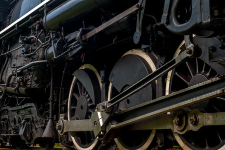 The driving wheels of a steam locomotive as it passes close at hand on the tracks photo